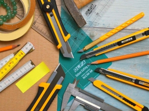 assorted type and size utility cutters on clear and green olfa measuring tool near adhesive tape rolls